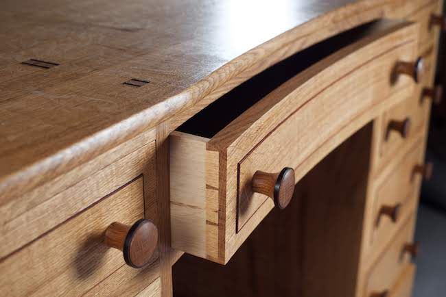 Handmade furniture detail of dovetails in a curved drawer